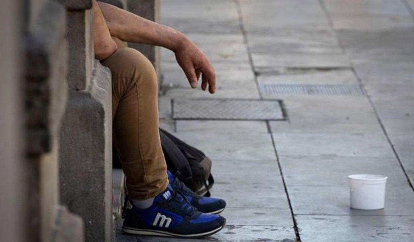 Un hombre pidiendo limosna en una calle de una ciudad española.