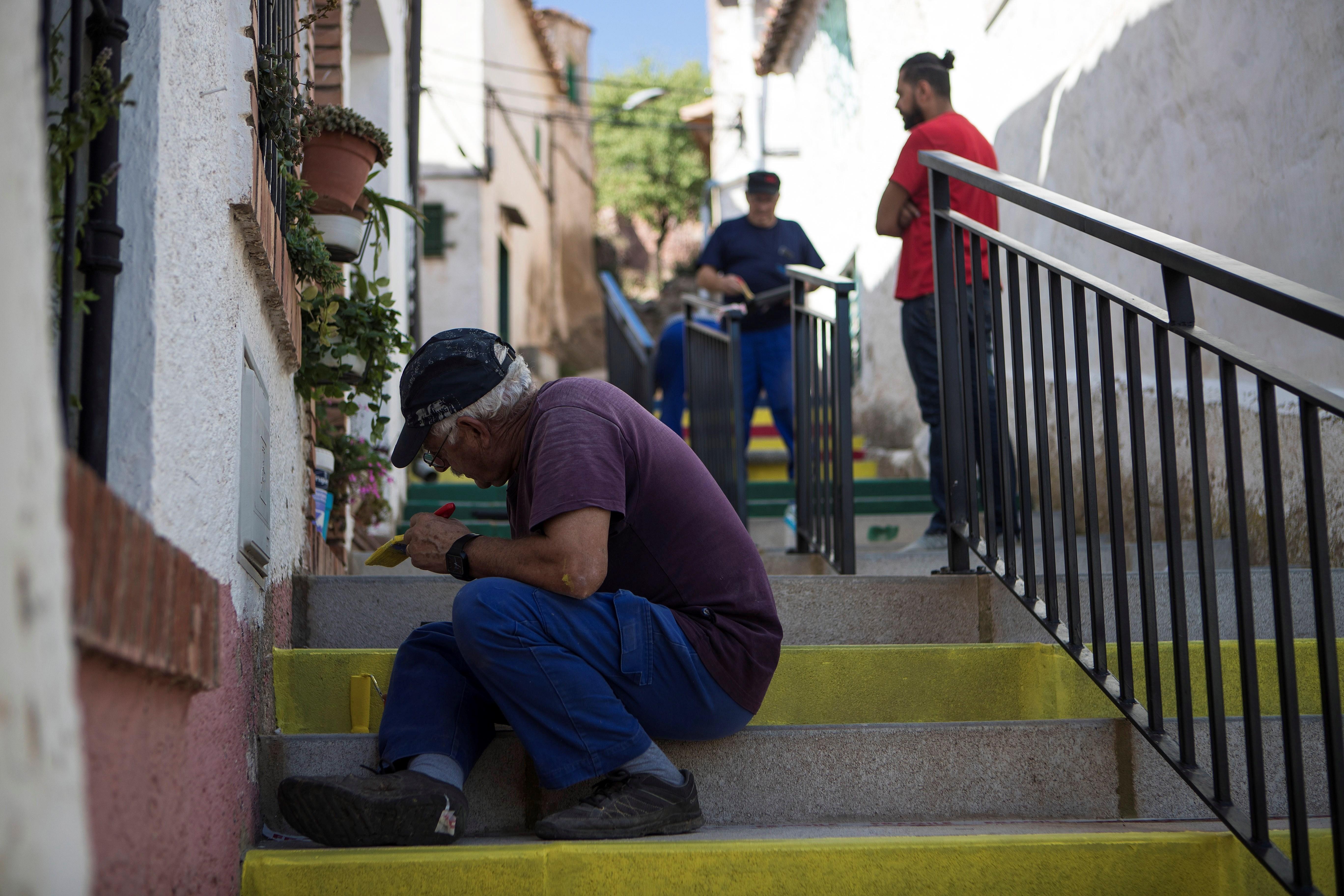 """Los vecinos ayudan a Khaïri Jemli a pintar una escalera de Aladrén con """"los colores de la alegría""""."""